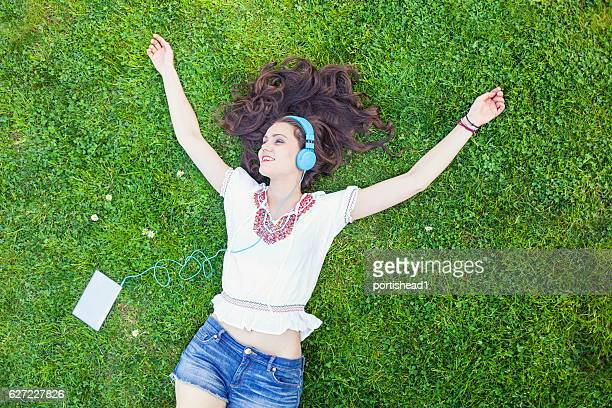 Carefree young woman lying down on grass and listening music