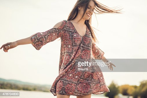 Carefree young woman spinning outdoors and having fun.
