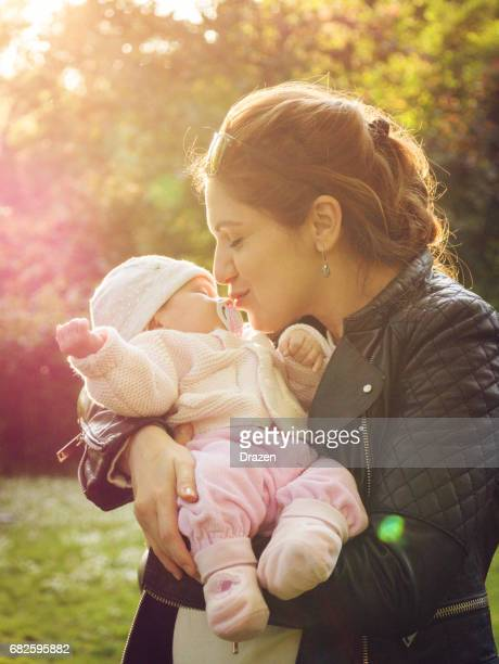 Careful mother with her baby in park on sunny day