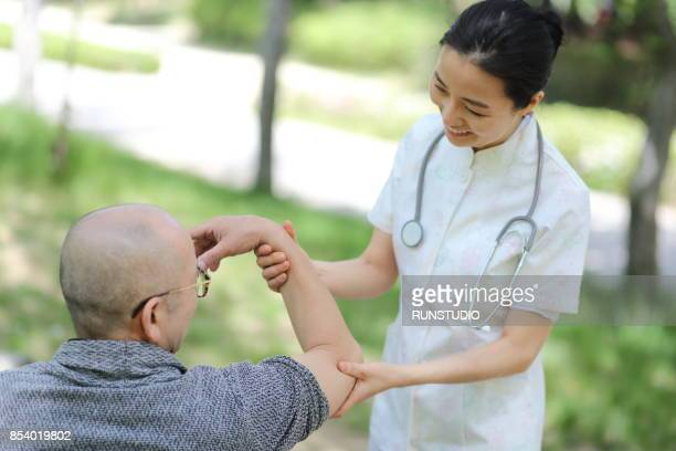careful nurse holding  senior man's arm