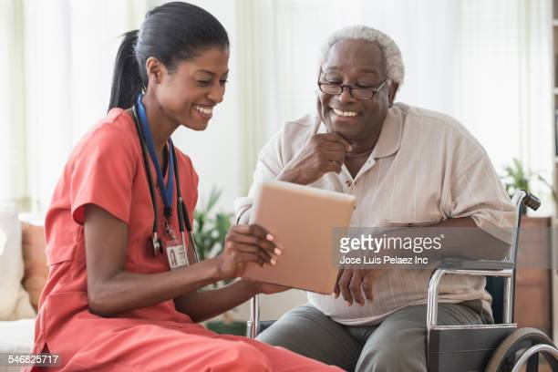 Caregiver and older man in wheelchair using digital tablet