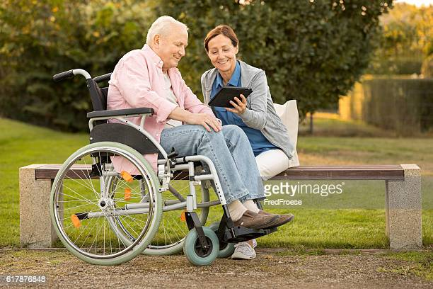 Caregiver and senior man on park bench, using digital tablet