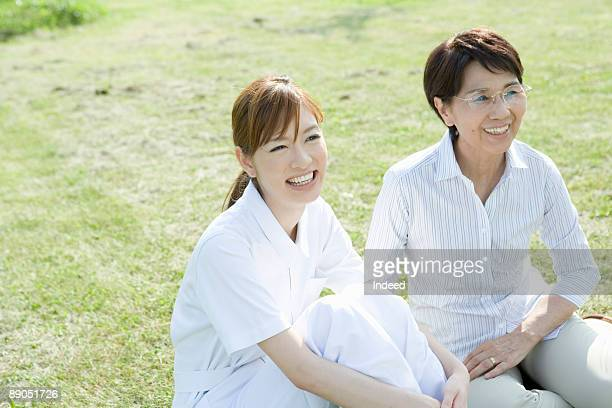 Caregiver and senior woman relaxing on grass