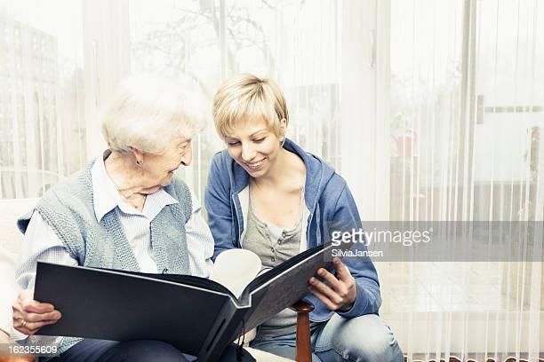 caregiver and senior woman sharing memories looking at photos