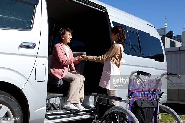 Caregiver assisting senior woman by van