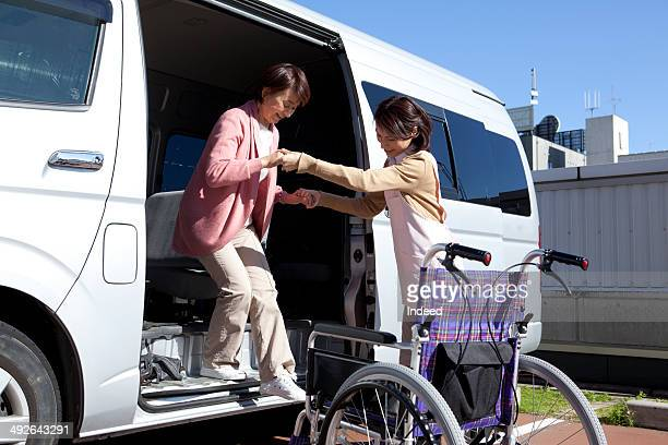 Caregiver assisting senior woman by van