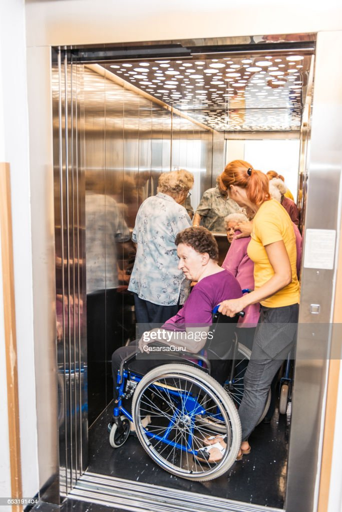 Caregiver Help Seniors At The Nursing Home To Stand In The Elevator : Stock Photo