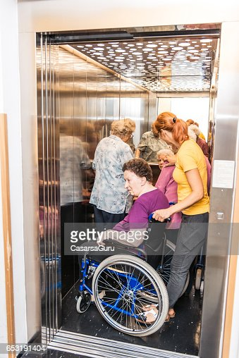 Caregiver Help Seniors At The Nursing Home To Stand In The Elevator : Stock-Foto