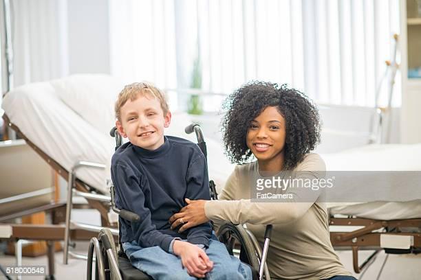 Caregiver Helping a Boy into a Wheelchair