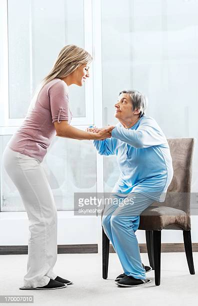 Caregiver helping a senior lady to get up.