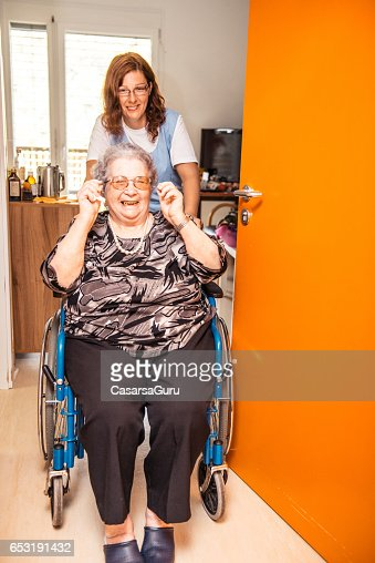 Caregiver Helping A Senior Woman On A Wheelchair In The Nursing Home : Stockfoto