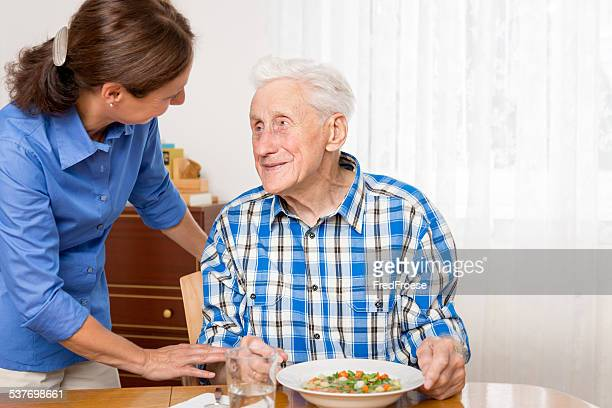 Caregiver helping senior man to eat