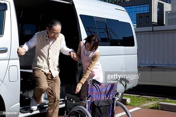 Caregiver helping senior man to get out of van
