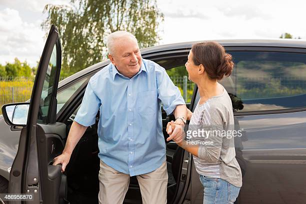Caregiver helping senior out of the car