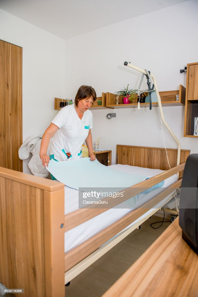 Caregiver In The Retirement Home Changing And Cleaning Seniors Bedroom : Stock Photo