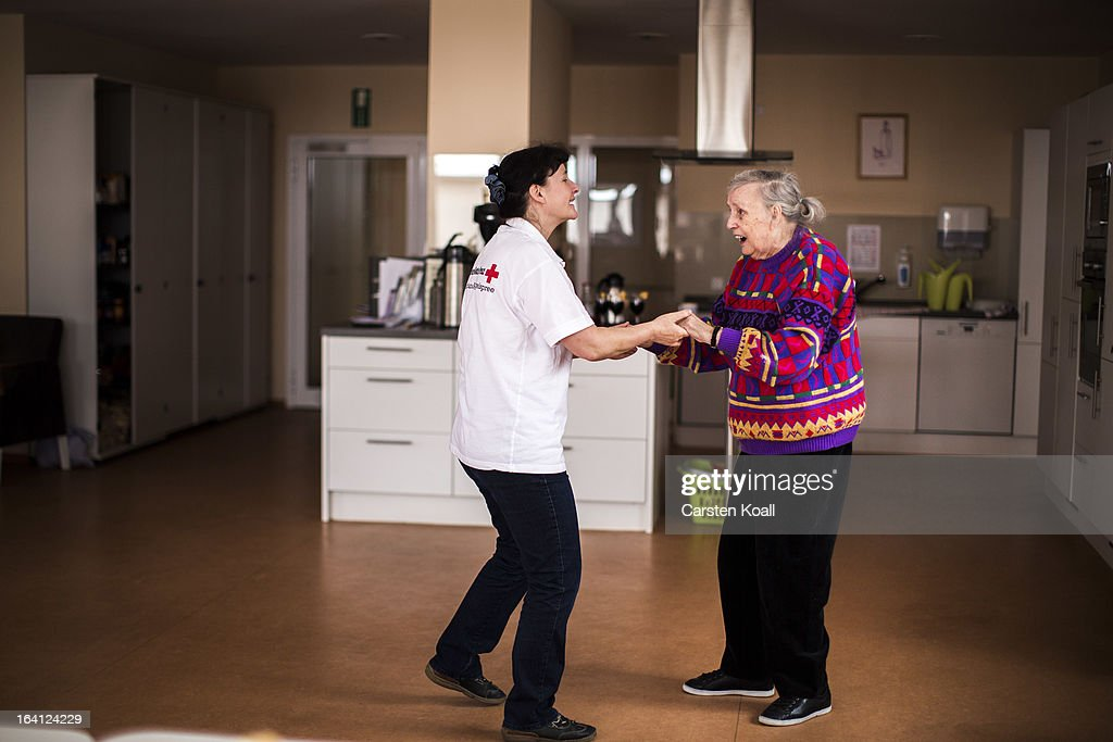 Caregiver Jolanta Spychalska (L) dances together with day guest Hannelore (R) in the geriatric day care facility of the German Red Cross (DRK, or Deutsches Rotes Kreuz) at Villa Albrecht on March 11, 2013 in Berlin, Germany. A great number of senior Citzens struggle with various forms of dementia at Villa Albrecht. The German Red Cross dates its origin back to 1863 with the founding of the Wuerttembergischer Sanitaetsverein, a medical association that provided care to wounded soldiers. Today the German Red Cross has four million members nationwide and is active in international aid and social care.