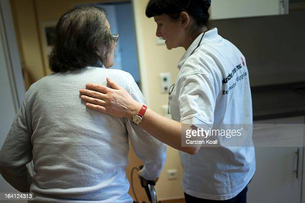 Caregiver Jolanta Spychalska puts her hand on the back of day guest Philippiene as she walks her walker in the geriatric day care facility of the...
