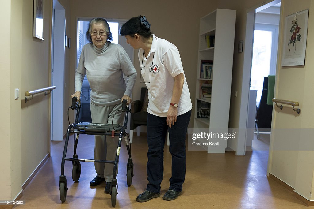 Caregiver Jolanta Spychalska (R) walks beside day guest Philippiene (L) as she walks her walker in the geriatric day care facility of the German Red Cross (DRK, or Deutsches Rotes Kreuz) at Villa Albrecht on March 18, 2013 in Berlin, Germany. A great number of senior Citzens struggle with various forms of dementia at Villa Albrecht. The German Red Cross dates its origin back to 1863 with the founding of the Wuerttembergischer Sanitaetsverein, a medical association that provided care to wounded soldiers. Today the German Red Cross has four million members nationwide and is active in international aid and social care.