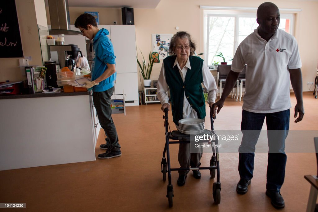 Caregiver Sekou Doumbouya (R) helps day guest Philippiene (C) to carry dishes on her walker to the table in the geriatric day care facility of the German Red Cross (DRK, or Deutsches Rotes Kreuz) at Villa Albrecht on March 11, 2013 in Berlin, Germany. A great number of senior Citzens struggle with various forms of dementia at Villa Albrecht. The German Red Cross dates its origin back to 1863 with the founding of the Wuerttembergischer Sanitaetsverein, a medical association that provided care to wounded soldiers. Today the German Red Cross has four million members nationwide and is active in international aid and social care.