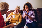 Elderly carer sitting with two of her patients in the care home. They are enjoying some cake and tea.
