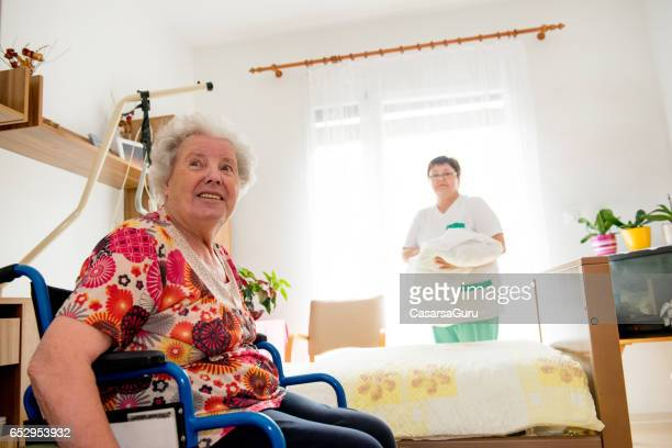 Caregiver Socializing With Senior Woman While Cleaning Her Room