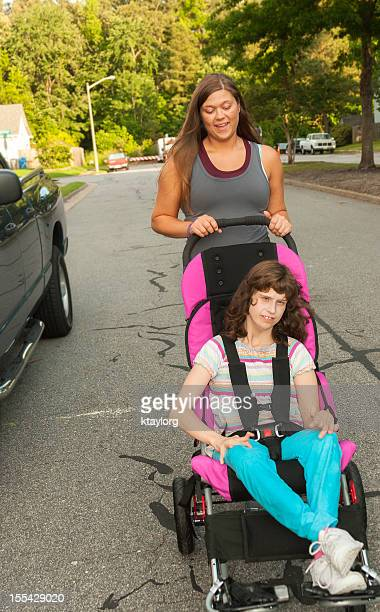 Caregiver takes disabled girl for a walk