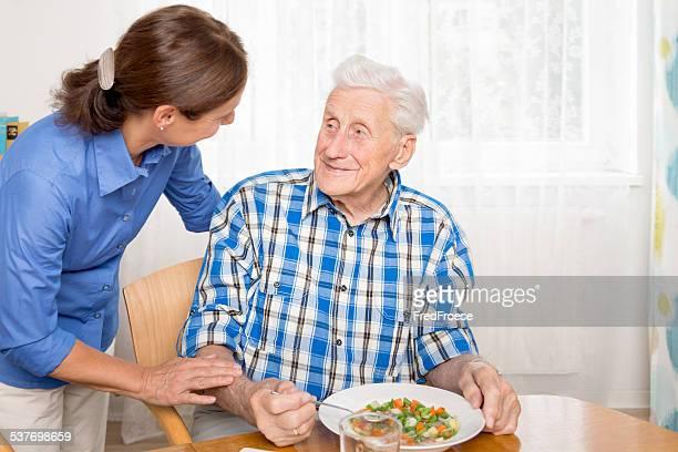Caregiver with senior man, helping eating