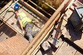 a builder or roofer has fallen from the top elevation of scaffold on a construction site and landed on the next level . He is grimacing in pain . The shot is focussed on the area that the roofer had b