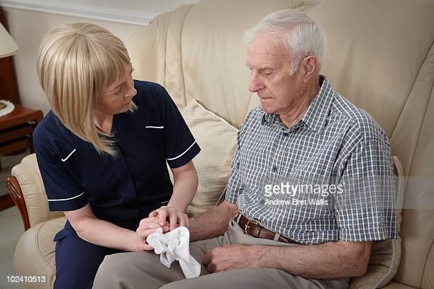 carer consoling upset elderly man