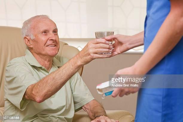 carer giving an elderly man water and pills