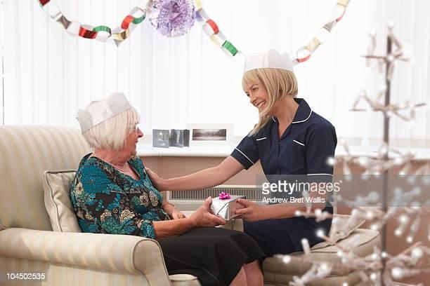 carer giving an elderly woman a Christmas gift