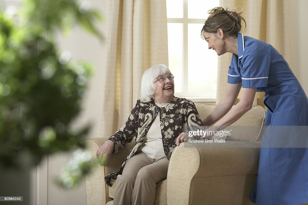 Carer helping elderly woman into a chair : Stock Photo