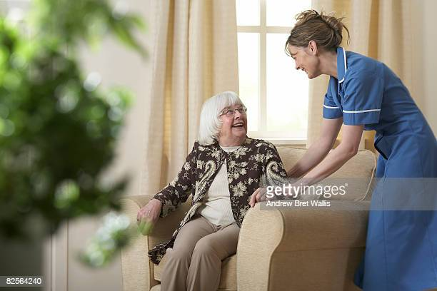 Carer helping elderly woman into a chair