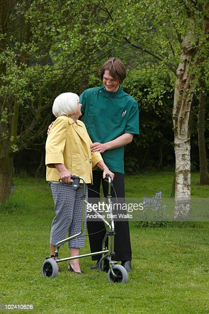 carer helping elderly woman to walk in a garden