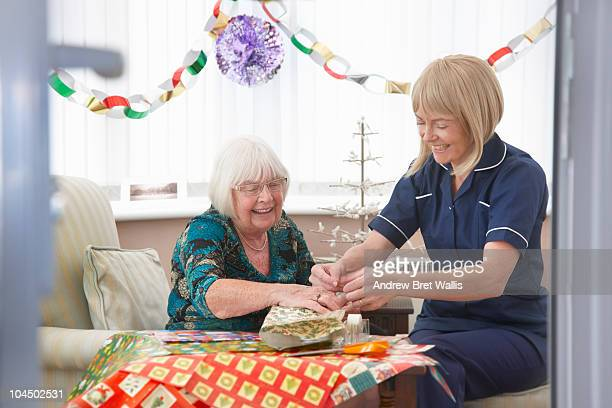 carer helping elderly woman wrap Christmas gifts