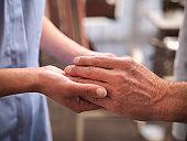Carer holding hand of senior man