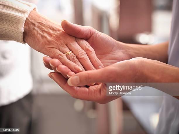 Carer holding hand of senior woman