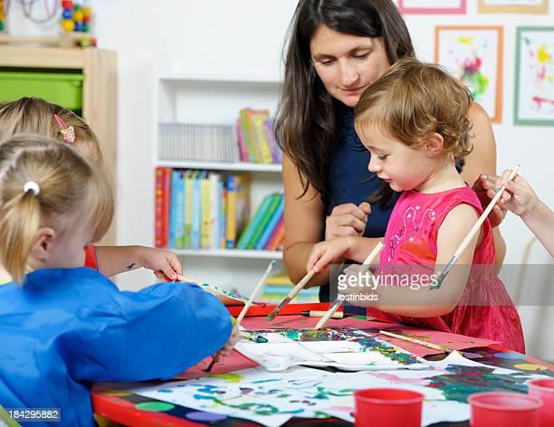 Carer interagir avec un groupe de jeunes enfants lors d'Art et d'artisanat
