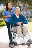 Carer Pushing Senior Man In Wheelchair