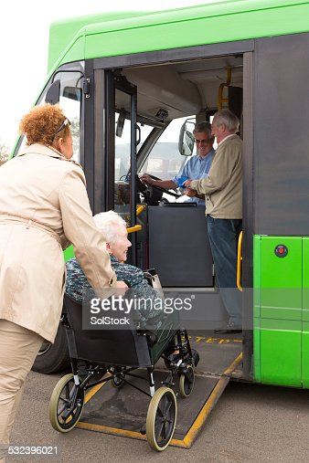 Carer Pushing Senior Woman onto Bus Via Wheelchair Ramp