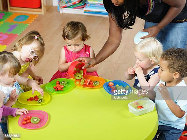 Carer Serving Fruit To Group Of Toddlers/ Children At Nursery