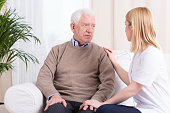 Young female carer supporting sad senior man