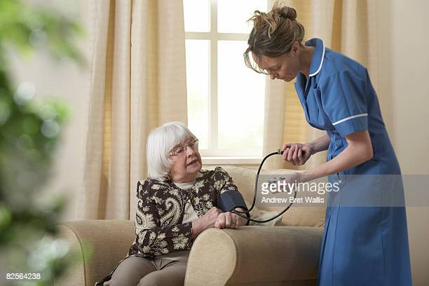 Carer taking elderly woman's bloodpressure