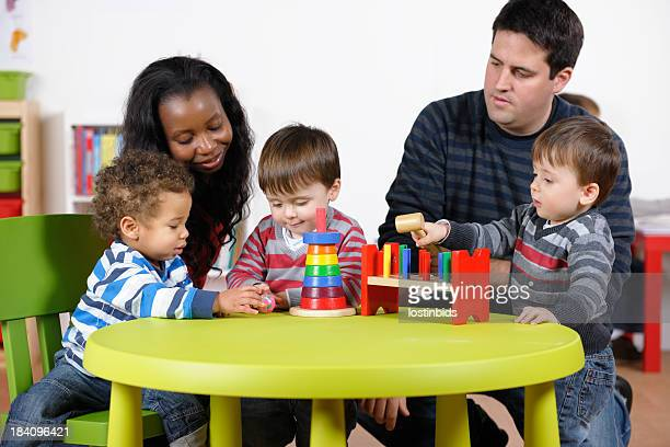 Carers Supervising Group Of Toddlers Using Developmental Toy At Playtime