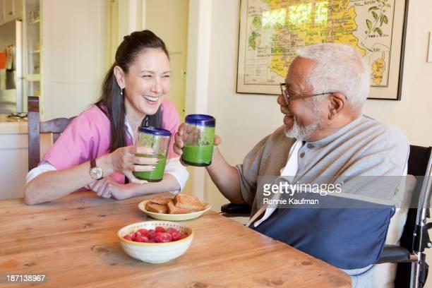 Caretaker and older man having smoothies