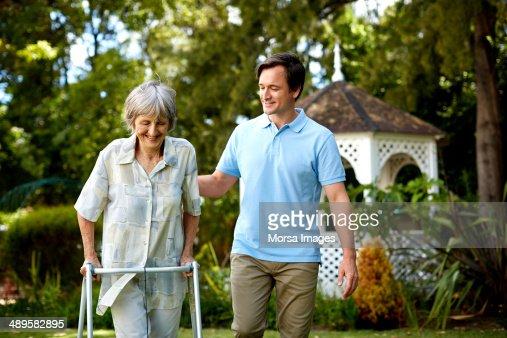Caretaker assisting senior woman in using walker