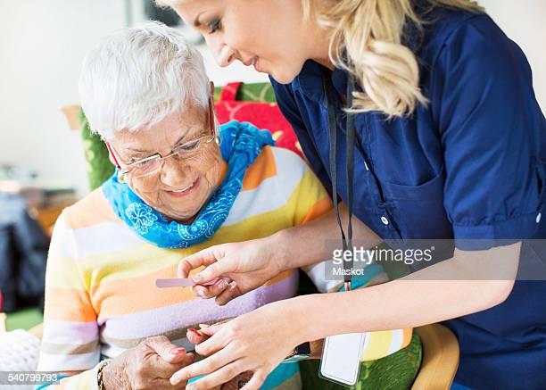 Caretaker filing senior womans fingernails at nursing home