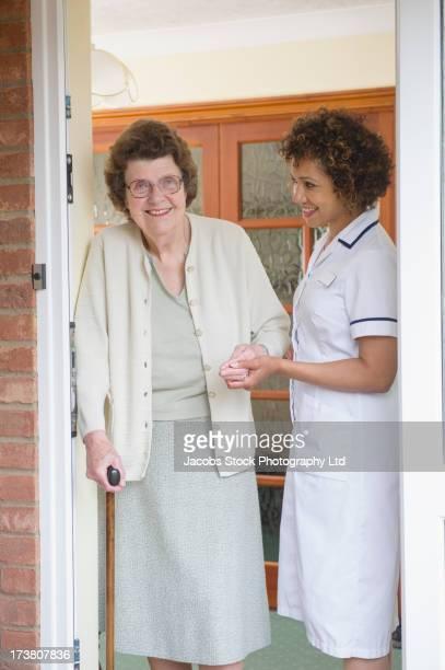 Caretaker helping older woman walk in house