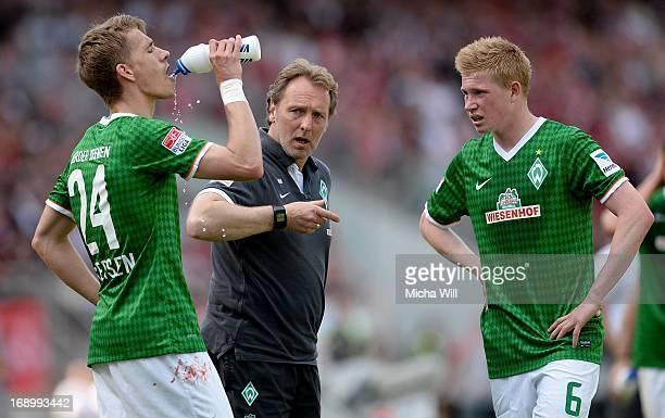 Caretaker manager Mathias Hoenerbach of Bremen speaks to Nils Petersen and Kevin de Bruyne of Bremen during a short break in he Bundesliga match...