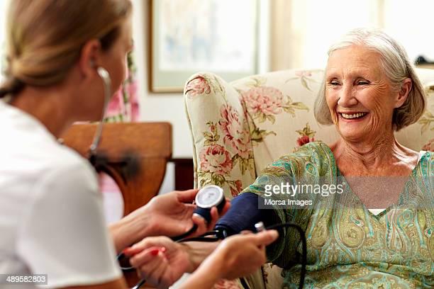 caretaker measuring senior women?s pressure